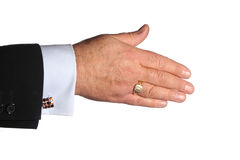 Outstretched Hand. Hand extended for handshake with blue shirt and cufflink, in dark jacket Stock Photo