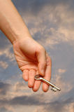 Outstretched hand holding key. Outstretched hand holding a house key on a cloudy sky background Stock Image