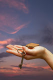 Outstretched palm. Holding a house key on a cloudy sky background Royalty Free Stock Photos