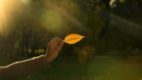 outubro escrito na folha dourada do outono, mão que guarda escritas, outono brilhante fotografia de stock