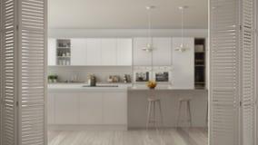 Ouverture blanche de porte de pliage sur la cuisine minimaliste moderne avec l'île, conception intérieure blanche, concept de con photos libres de droits