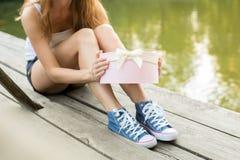 Ouverture d'un cadeau sur un emplacement en bois Images libres de droits
