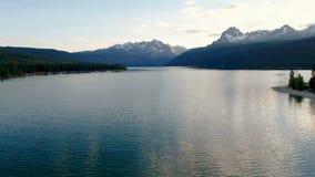 Ouvre une session un lac avec la réflexion de montagne pendant que le soleil place banque de vidéos