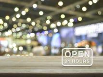 Ouvrez 24 heures d'icône sur la table en bois au-dessus de la lumière de tache floue et de l'ombre de Images libres de droits