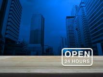 Ouvrez 24 heures d'icône sur la table en bois au-dessus de la tour moderne de ville de bureau Photos stock