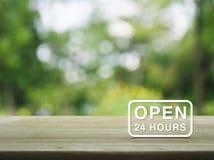 Ouvrez 24 heures d'icône sur la table en bois au-dessus du backgrou d'arbre de vert de tache floue Images libres de droits