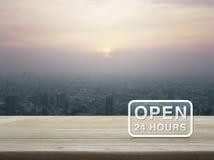 Ouvrez 24 heures d'icône sur la table en bois Photo libre de droits