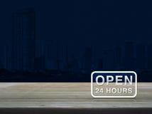 Ouvrez 24 heures d'icône sur la table en bois au-dessus de la tour moderne de ville de bureau Images stock