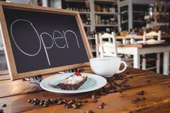 Ouvrez l'enseigne avec la tranche de tasse de gâteau et de café sur une table Photos stock