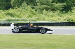 Ouvrez l'entraînement de voiture de course noir d'habitacle sur la voie Image libre de droits