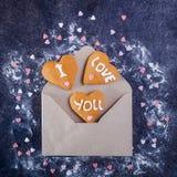 Ouvrez l'enveloppe de papier de métier avec les biscuits faits maison en forme de coeur de gingembre avec je t'aime l'inscription Photos stock