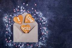 Ouvrez l'enveloppe de papier de métier avec les biscuits faits maison en forme de coeur de gingembre avec je t'aime l'inscription Photographie stock libre de droits