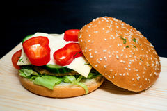 Ouvrez l'hamburger avec le poivre, le fromage, le concombre, le sésame et les verts Photographie stock