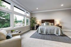 Ouvrez l'intérieur moderne de chambre à coucher avec de grandes fenêtres et murs gris photos libres de droits