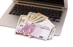 Ouvrez l'ordinateur portable avec les dollars et l'euro argent Image stock