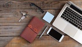 Ouvrez l'ordinateur portable, le téléphone intelligent, les verres, le carnet et les clés Concept d'espace de travail Images libres de droits