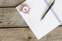 Ouvrez l'ordre du jour de carnet avec l'horaire et la petite horloge rose à 8h00 Photographie stock libre de droits