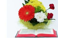 Ouvrez la bible, et les belles fleurs sur le fond blanc Photos stock