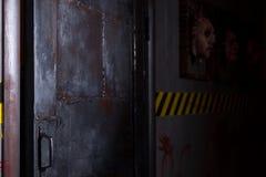 Ouvrez la grande porte noire près des visages horribles coincés dans les cadres ab de place Photo libre de droits