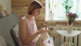 Ouvrez la laine de tricotage de femme se reposant sur le divan dans la chambre sur la fenêtre de fond clips vidéos