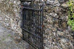Ouvrez la porte noire en métal et le mur en pierre Image stock