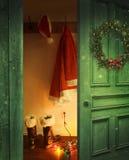Ouvrez la porte rustique avec l'équipement de Santa accrochant sur des crochets photo stock