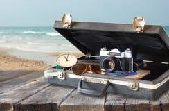Ouvrez la valise avec de vieilles lunettes de soleil et horloge d'appareil-photo Photographie stock libre de droits