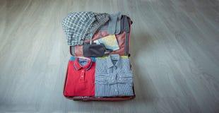 Ouvrez la valise avec des vêtements sur le plancher en bois photo libre de droits
