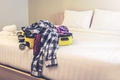 Ouvrez la valise de voyage avec des vêtements et des accessoires sur le lit photos libres de droits