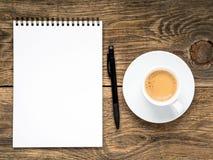 ouvrez le bloc-notes avec la tasse de spirale, de stylo et de café sur la vieille table en bois Photographie stock