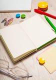 Ouvrez le bloc-notes avec les pages vides sur la table avec des outils de bureau Photo stock
