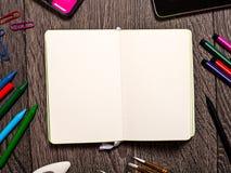 Ouvrez le bloc-notes avec les pages vides sur la table avec des outils de bureau Images stock