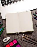 Ouvrez le bloc-notes avec les pages vides sur la table avec des outils de bureau Image stock