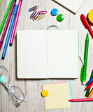 Ouvrez le bloc-notes avec les pages vides sur la table avec des outils de bureau Photos stock