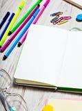 Ouvrez le bloc-notes avec les pages vides sur la table avec des outils de bureau Photographie stock libre de droits