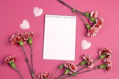 Ouvrez le bloc-notes vide avec des fleurs d'oeillets sur un backgrou fuchsia Photographie stock libre de droits