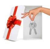 Ouvrez le boîte-cadeau avec la main et les clés sur le blanc Photo libre de droits