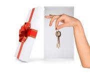 Ouvrez le boîte-cadeau avec le bras et les clés sur le blanc Photos stock