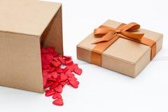 Ouvrez le boîte-cadeau hors dont tombe beaucoup de coeurs rouges sur le fond en bois blanc Photographie stock libre de droits