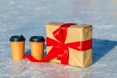 Ouvrez le cadeau avec le ruban rouge et les tasses de café sur la patinoire Image stock