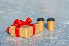 Ouvrez le cadeau avec le ruban rouge et les tasses de café sur la patinoire Image libre de droits