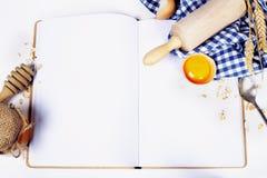 Ouvrez le cahier et les ingrédients fondamentaux de traitement au four Photo libre de droits