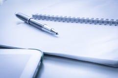 Ouvrez le carnet avec le stylo et le comprimé de boule métalliques Photographie stock