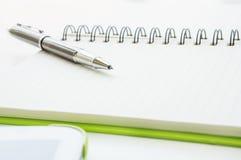 Ouvrez le carnet avec le stylo et le comprimé de boule métalliques Photos stock