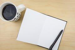 Ouvrez le carnet avec le stylo noir et une tasse de café Photo libre de droits