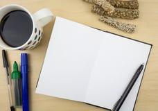 Ouvrez le carnet avec le stylo, une tasse de café et quelques bâtons avec des graines Image libre de droits