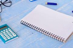 Ouvrez le carnet avec les pages vides avec la calculatrice, le stylo et les verres Photo libre de droits