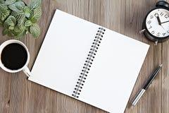 Ouvrez le carnet avec les pages vides, la tasse de café et l'horloge sur la table en bois de bureau, la vue supérieure ou la conf Photos libres de droits