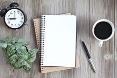 Ouvrez le carnet avec les pages vides, la tasse de café et l'horloge sur la table en bois de bureau, la vue supérieure ou la conf Photos stock