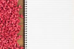 Ouvrez le carnet de page vide avec de petits coeurs de papier rouges photos stock